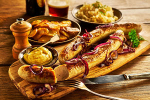 Bratwurst sausage on wooden board with potatoes and mustard on the side